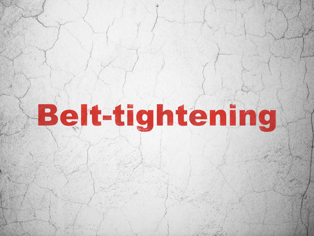 Finance concept: Red Belt-tightening on textured concrete wall background