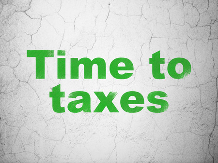 Time concept: Green Time To Taxes on textured concrete wall background Stock Photo