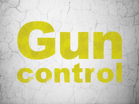 Privacy concept: Yellow Gun Control on textured concrete wall background