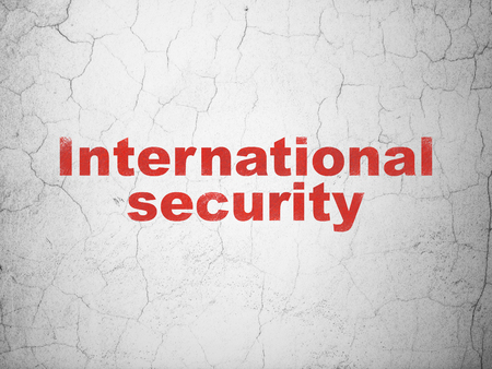 Protection concept: Red International Security on textured concrete wall background Reklamní fotografie