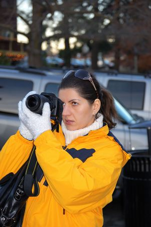 夕方にナイス シュートを作る黄色のジャケットで若い女性ジャーナリストのカメラマン。