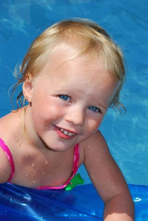 Fun happy little girl after swimmimg looking from pool.  photo