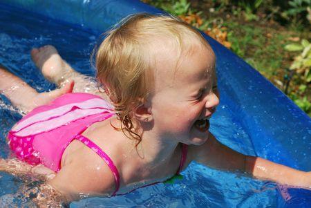 Fun happy little girl swimming in pool. photo