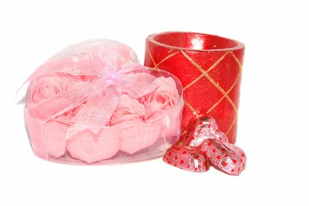 plastic heart: Pink little roses are in the plastic heart box with red candle and chocolate sweets.