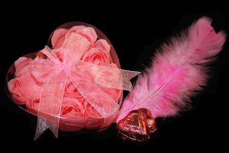 plastic heart: Le rose sono rosa poco nel cuore di plastica scatola con piuma e dolci. Archivio Fotografico
