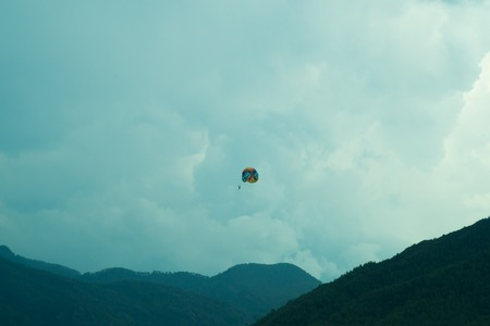 Skydiver flying with a colorful parachute Standard-Bild
