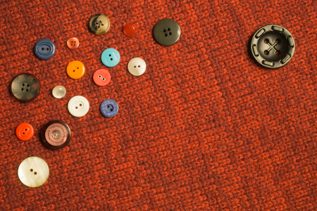 Various sewing buttons on textile background. copy space