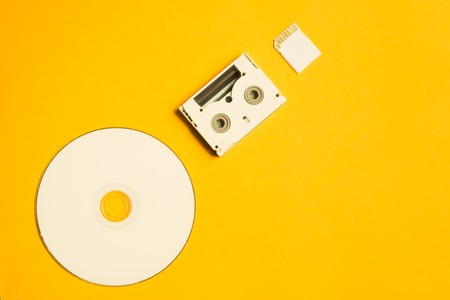 Compact disc and memory card on yellow background. digital video cassette. copy space Stock Photo