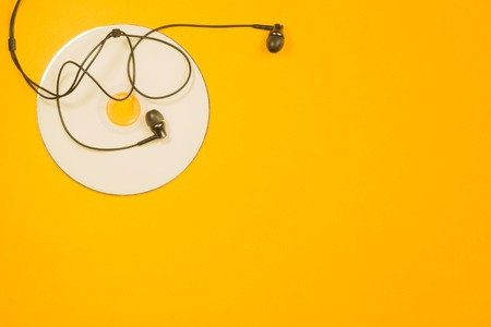 Earphones and compact disk on yellow background. copy space