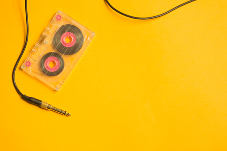 Retro cassette tape and audio jack on the yellow background. copy space