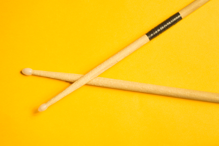 Used drumsticks isolated on yellow background. copy space