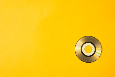 Mini compact disc on yellow background. copy space Stock Photo