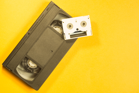 Video cassette on yellow background. mini cassette. copy space