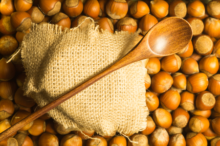 Honey pot under cloth with wooden spoon and nuts background