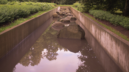 Pond channel with stones in park background Imagens