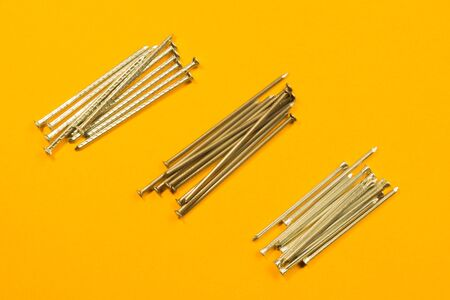 Metal nails isolated on yellow background