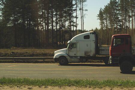 Big truck on the roadside near forest. white lorry on a road. transport vehicle Foto de archivo - 129828247
