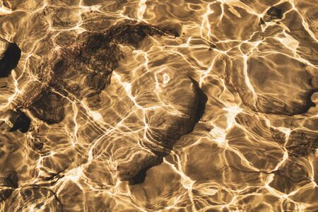 Shiny transparent water. clear water with pebbles and stone on the bottom. shining reflections of sun rays and ripples on the water surface