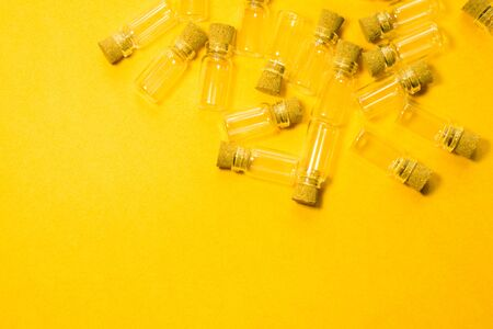 Empty little bottles with cork stopper isolated on yellow. glass vessels. transparent containers. test tubes. copy space Stok Fotoğraf