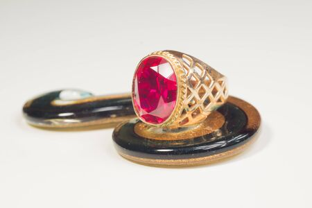 Golden ring with the ruby isolated on white. jewelry background Фото со стока