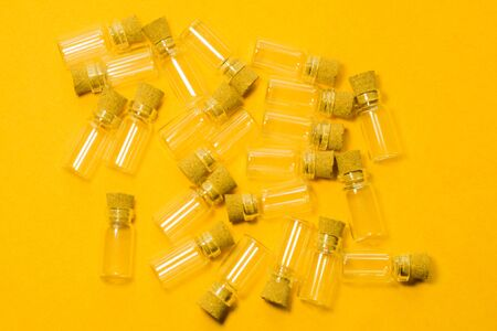 Empty little bottles with cork stopper isolated on yellow. glass vessels. transparent containers. test tubes Stockfoto