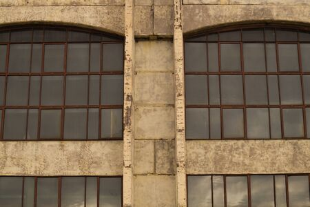 Big windows of the factory on the cement wall background
