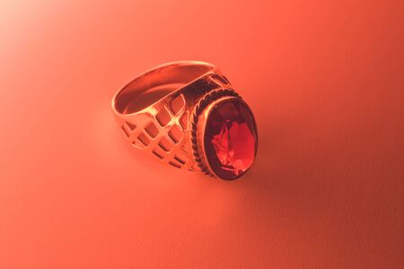 Golden ring with ruby under red light background