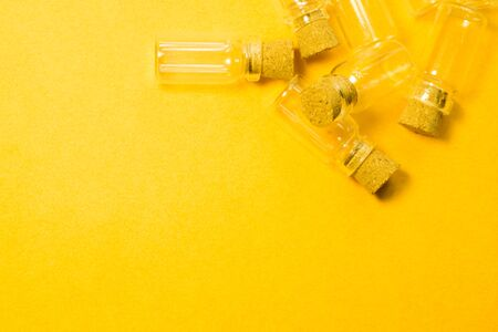 Empty little bottles with cork stopper isolated on yellow. glass vessels. transparent containers. test tubes. copy space Stockfoto