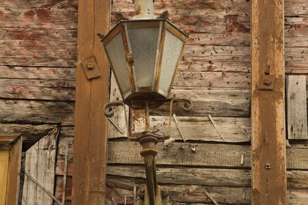 Windows of the old wooden house. wooden plank wall with vintage lamp
