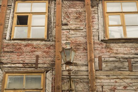 Windows of the old wooden house. wooden plank wall with windows and vintage lamp