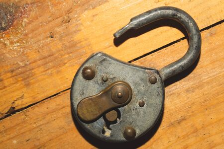 Old rusty lock on a wooden table. Vintage padlock on wood background Imagens