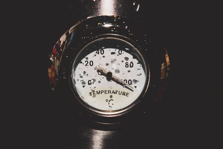 Retro style analog thermometer on the metal background. high temperature concept Imagens