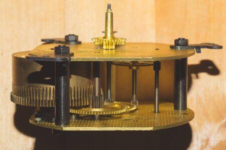 Uhrwerk auf Holztisch. Detail der Zahnräder einer mechanischen Uhr Standard-Bild