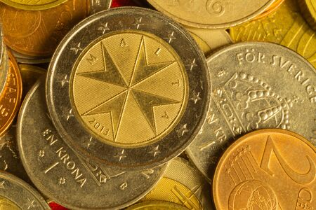 Coins of different countries. a lot of metal coins of different denominations and various countries. financial background. euro coin in the foreground