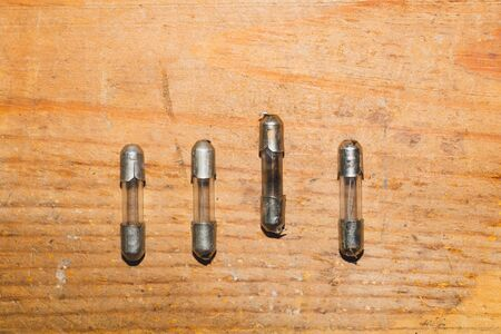 Row of fuses with burned out fuse on wooden background. safety device for overcurrent protection. protection of an electrical circuit Foto de archivo