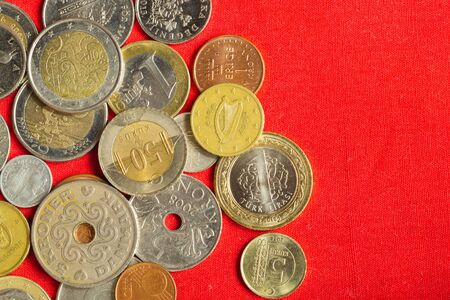 Coins of the different countries on the red background. many metal coins of different denominations and various countries. finance background. copy space