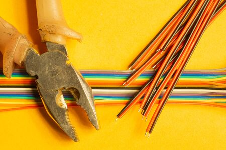 Pliers and colorful wires on yellow background. work tool