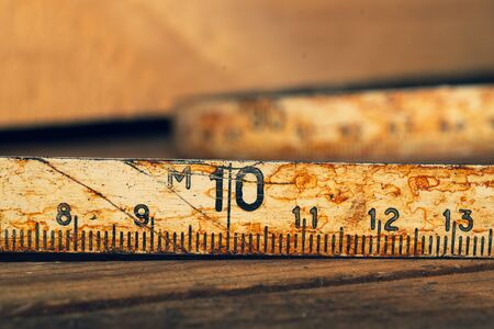 Old rusty ruler with black numbers on a working wooden table. vintage measuring tape close up. industrial background. carpentry workbench 免版税图像