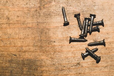 Screws on a wooden background.working tools. copy space Foto de archivo