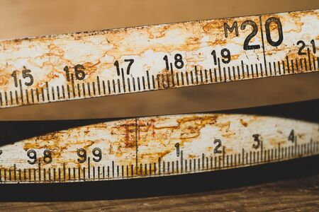 Old rusty ruler with black numbers on a working wooden table. vintage measuring tape close up. industrial background. carpentry workbench Imagens