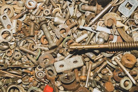 Pile of fasteners and screws close up. scrap metal. different metal parts. industrial background