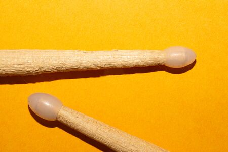 Pair of drumsticks on yellow background close up. copy space