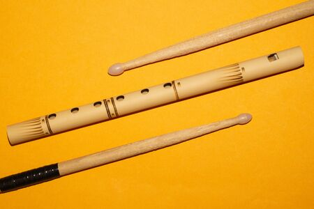 Bamboo bansuri flute and drumsticks. simple music instruments