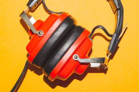 Vintage red headphones on yellow background. retro earphones