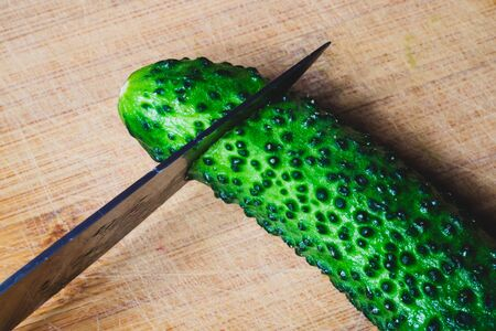 Cucumber and knife on a wooden cutting board. vegetable slicing process. cooking food