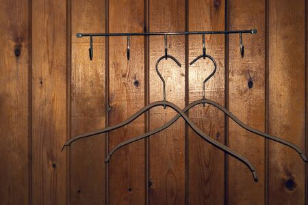 Hangers on wooden wall. dress rack Stock Photo