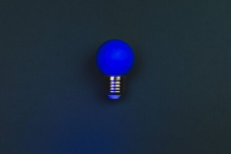 Blue light bulb on the dark background. single bulb with copy space