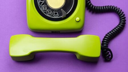 Classic phone with handset. vintage green telephone with phone receiver isolated on purple background. old communication technology. copy space