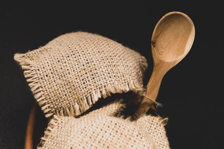 Honey pots with linen cloth with wooden spoon on dark background
