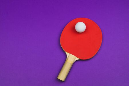 Red table tennis racket with a ball isolated on a colored background.